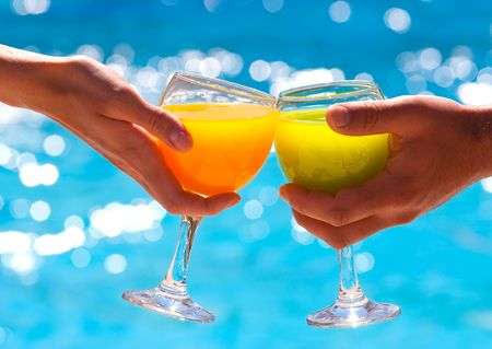 Two hands hold glasses with juice against blue water