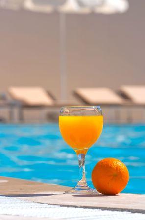 brink: Orange and glass with orange juice on the brink of pool