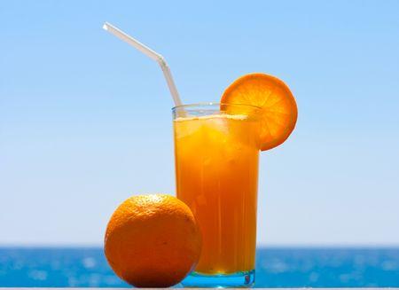 Glass of fresh orange juice and orange against the sea photo