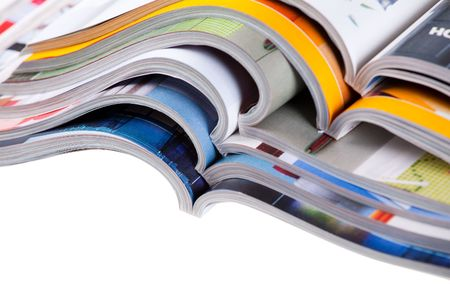 publication: Pile of colour illustrated magazines on white background. Isolated.