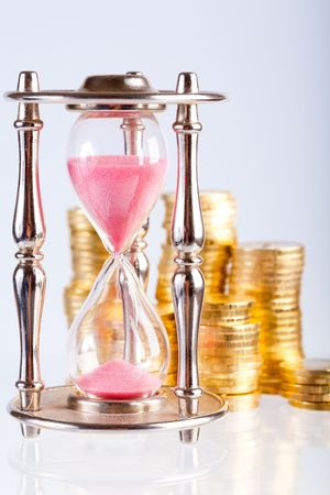 Time is money concept - hourglass and coins   Stock Photo