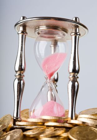 trickling: Time is money concept - hourglass and coins   Stock Photo