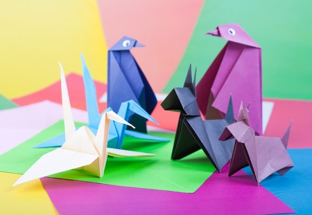 Origami. Figures of birds and animals against colour paper photo