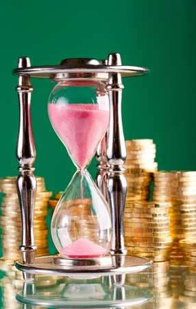 timely: Time is money concept - hourglass and coins   Stock Photo