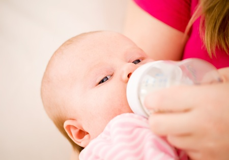 Feeding of the chest baby by a dairy mix from a childrens small bottle photo