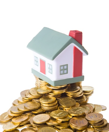 Toy small house standing on a heap of coins. The concept of purchase of habitation Stock Photo - 8910328