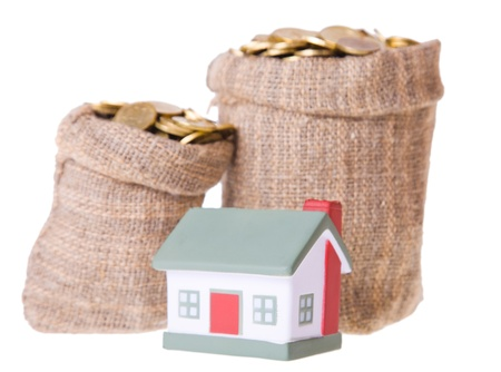 Toy small  house and bags with money. The concept of purchase of habitation Stock Photo - 8910313