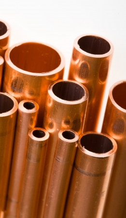 Set of copper pipes of different diameter lying in one heap Stock Photo