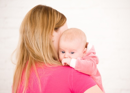 Young mum holds on hands of the chest baby photo