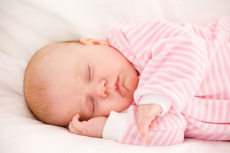 sleeping baby in striped toddlers close up Foto de archivo