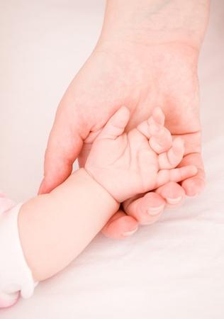 babyvoetjes: ouderlijke hand houdt hand de baby