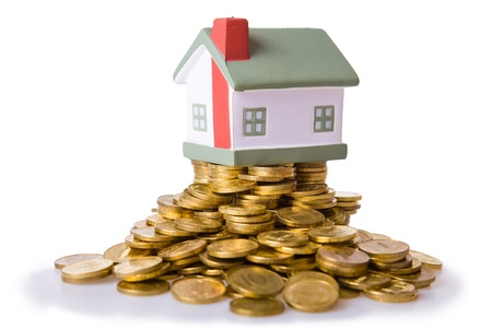 Toy small house standing on a heap of coins. The concept of purchase of habitation Stock Photo - 9060341