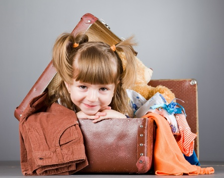 joyfully: four-year girl joyfully sits in an old suitcase with toys and clothes
