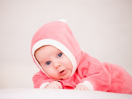 baby in is bright-pink overalls lies on a stomach