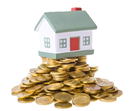 Toy small house standing on a heap of coins. The concept of purchase of habitation Stock Photo - 9139114