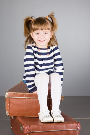 four-year beautiful girl sits on an old suitcase on a gray background Stock Photo - 9139149