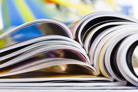 Closeup background of a pile of old magazines with bending pages photo
