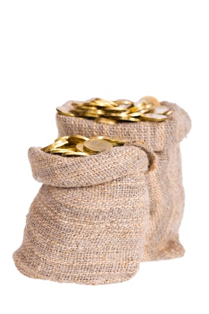Bags filled with coins. A white background. Isolated. Foto de archivo