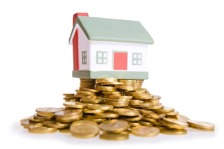 Toy small house standing on a heap of coins. The concept of purchase of habitation Stock Photo - 9708864