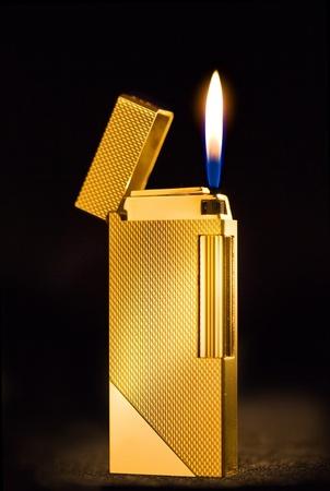 gas lighter: Elegant golden gas lighter against a dark background