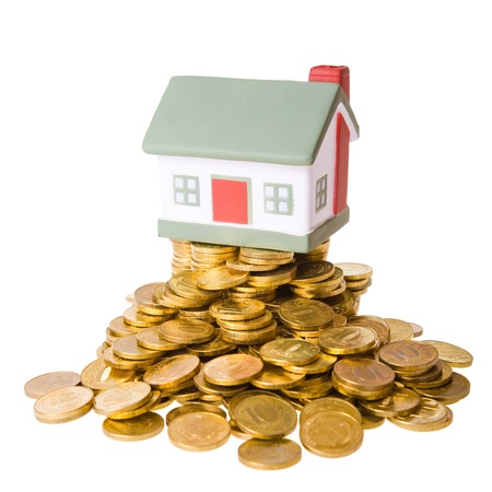 Toy small house standing on a heap of coins. The concept of purchase of habitation photo