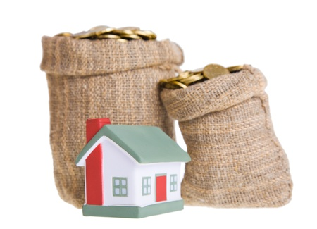 Toy small  house and bags with money. The concept of purchase of habitation photo