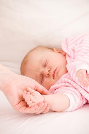 Mum holds by the hand the sleeping baby. Zdjęcie Seryjne