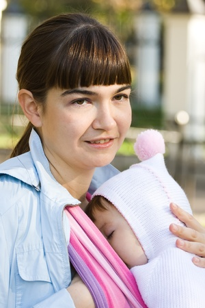 6 12 months: Walk with the child in a baby sling. Breastfeeding Stock Photo