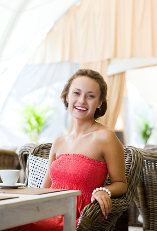 Young girl in a pink dress seated at a table in the summer restaurant Stock Photo - 10574477