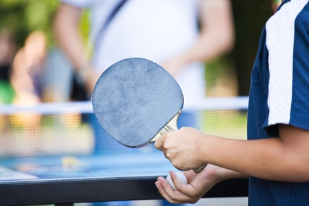 teenager in a dark blue vest plays park in Ping-Pong photo