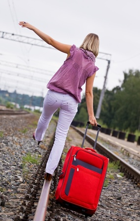 young woman with a red suitcase is on the railway tracks photo