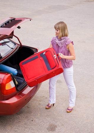 young woman puts the suitcase in the trunk of a car Stock Photo
