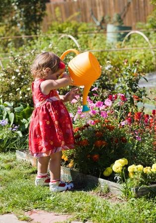Little girl watering flower beds