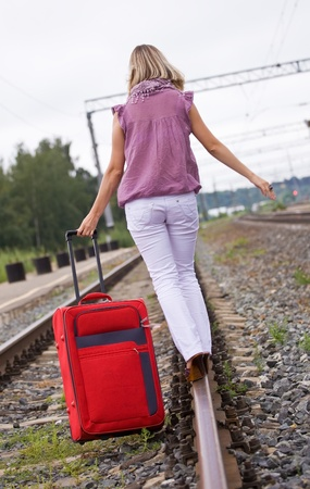 young woman with a red suitcase is on the railway tracks Stock Photo - 11890405
