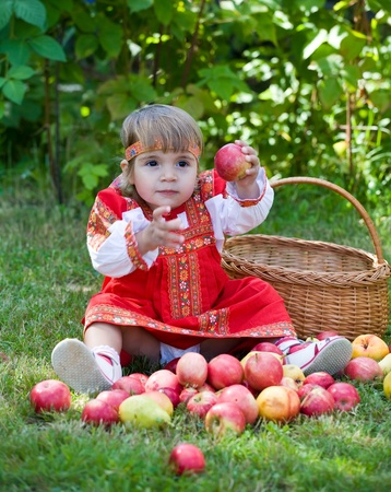 little girl collects the apples scattered on a grass in a basket  Stock Photo - 11956257