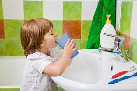 rinsing: Personal hygiene. The little girl rinses a mouth after toothbrushing.
