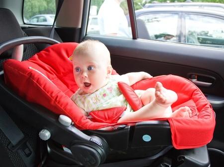 enfant banc: Petit enfant est assis dans le fauteuil automobile, fix� par les ceintures de s�curit�.