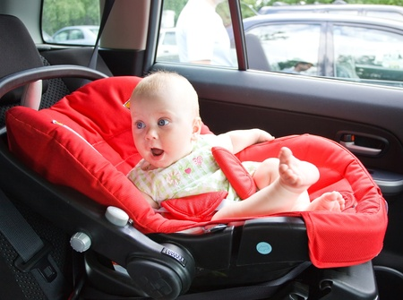 Small child sits in the automobile armchair, fastened by seat belts. photo