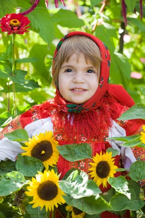 little girl in a smart Sarafan is among sunflowers photo