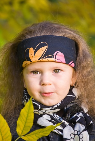 bandana girl: little girl in a black leather jacket and bandana in the autumn park Stock Photo