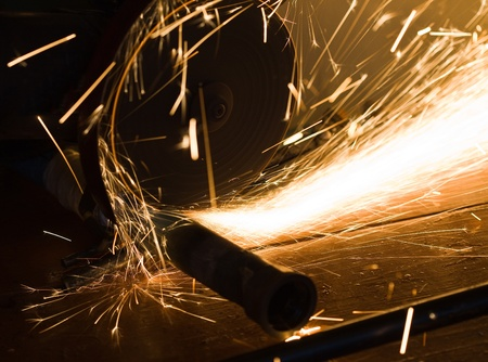 worker cuts a metal pipe by means of the abrasive tool Stock Photo - 12301873