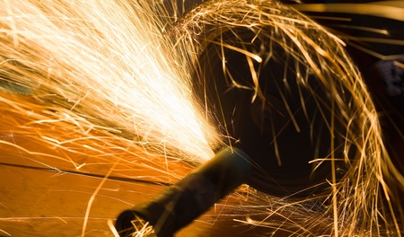 worker cuts a metal pipe by means of the abrasive tool photo