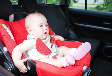 Small child sits in the automobile armchair, fastened by seat belts  photo