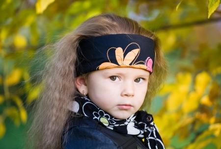 bandana girl: petite fille dans une veste en cuir noir et bandana dans le parc automne