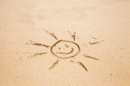 Drawing of the smiling sun on sand Stock Photo - 14288020