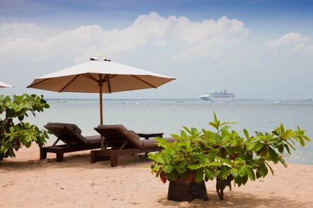 Chaise lounges and umbrella on an ocean coast. Summer holiday in the resort. photo
