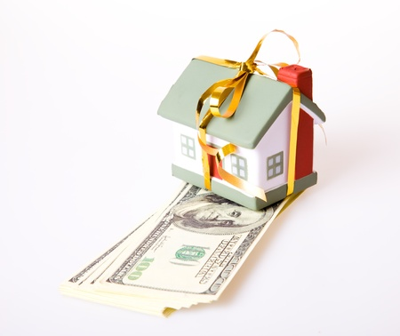 habitation: Toy small house with a gold bow. The concept of purchase and sale of habitation. Stock Photo