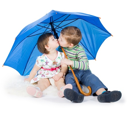 brother and the sister sit under a blue umbrella photo