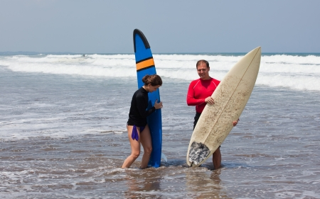 young man and the girl with boards for surf on an ocean coast photo