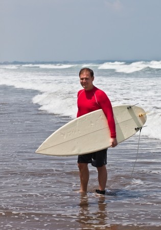 young man goes on an ocean coast with a board for surf photo